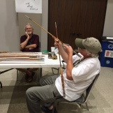 Clarke checking craftmanship of a bamboo rod at 2015 Mini-Expo