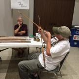 Clarke checking craftmanship of a bamboo rod at 2015 Mini-Expo